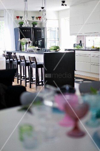 View across dining table to kitchen island with black worksurface and wooden bar stools in modern, open-plan kitchen area