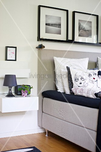Scatter cushions with comic-style covers on bed with upholstered headboard below framed pictures on wall; table lamp on floating bedside cabinet
