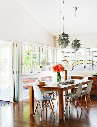 Bauhaus shell chairs around wooden table below Poulsen pendant lamps in rustic atmosphere