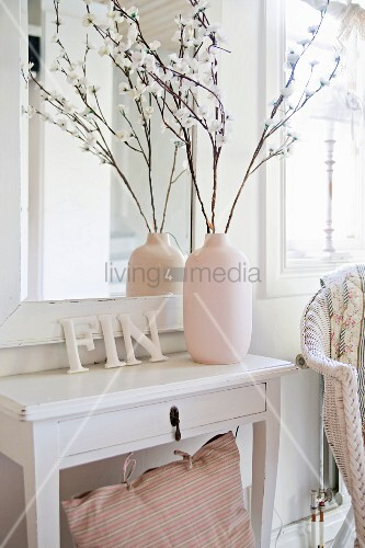 Vase of twigs and ornamental letters on white console table below ...