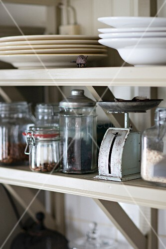 Storage jars and plates on open-fronted shelves