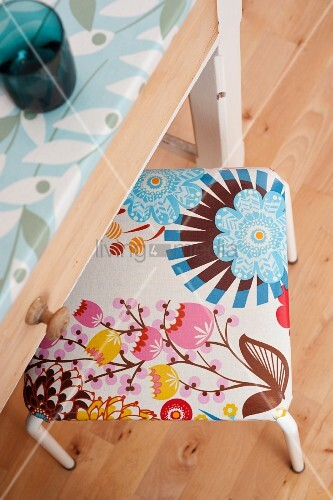 Stool upholstered in patterned oilcloth half under kitchen table