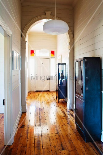 Hallway with arch, white wood-clad walls, blue vintage metal cabinets and rustic wooden floor