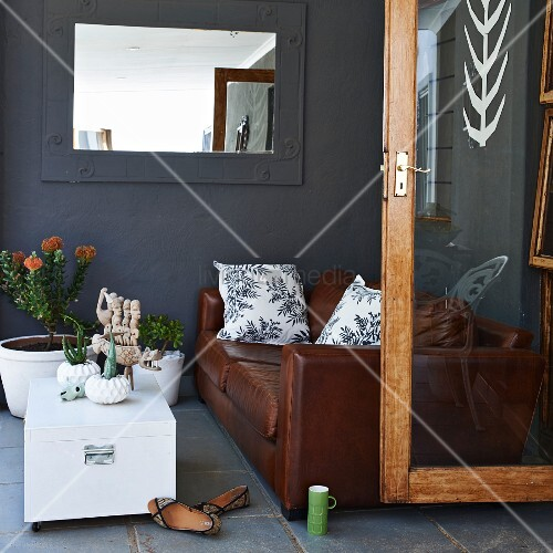 Seating area with brown leather sofa, white trunk table, potted plants and mirror with frame painted the same slate grey as wall; open glass door to one side