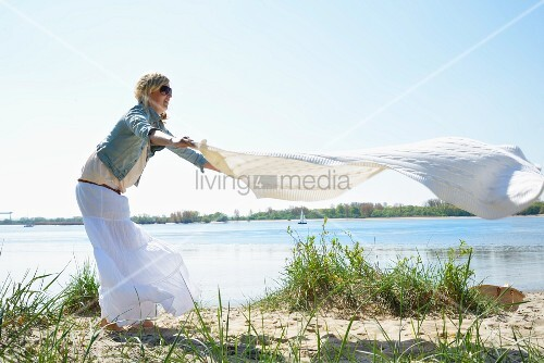 Woman spreading picnic blanket on beach