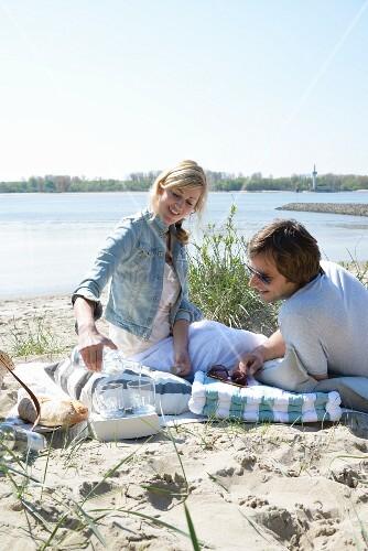 A couple having a picnic on the beach