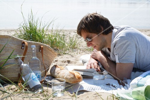 Man on a beach picnic reading a book