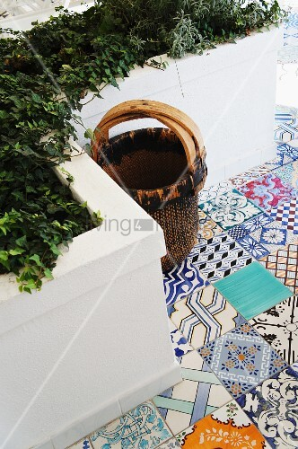 Basket on Mediterranean terrace with colourful, patterned floor tiles and masonry raised beds