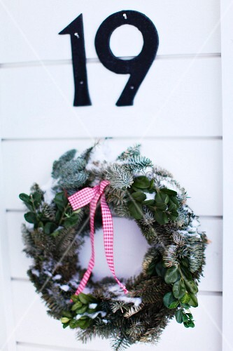 Christmas wreath of fir branches and ribbon on white wooden door below house number