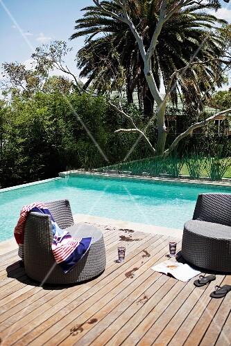Abkühlen im Pool - Dunkelbraune Rattan Outdoorsessel auf Holzdeck vor Pool in tropischem Garten