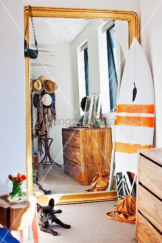 Full-length gilt-framed mirror leaned against wall next to surfboard in niche