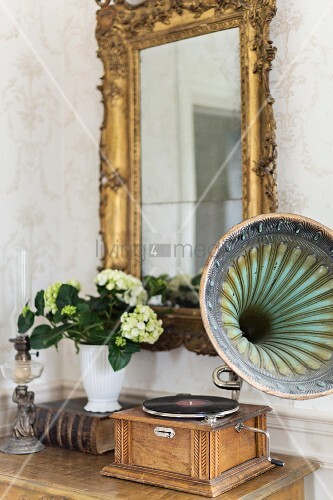 Vintage gramophone on console table below gilt-framed mirror on wall