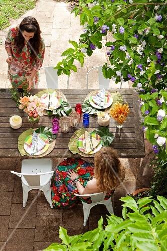Two women sitting at set garden table below flowering shrub in summery garden party atmosphere