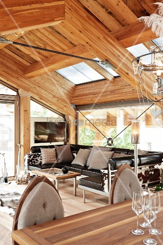 Open-plan interior with leather sofa in modern chalet with exposed ...