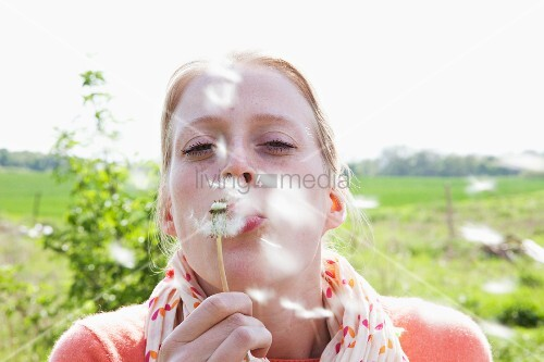 A woman blowing a dandelion clock