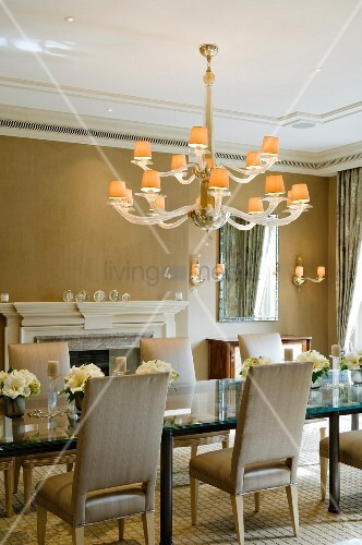 Elegant dining room with fireplace and illuminated chandelier above long glass table in historical, English manor house