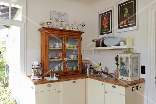 Küche mit kleinen Vitrinen auf Holz Arbeitsplatte, darunter Unterschränke mit cremefarbenen Fronten