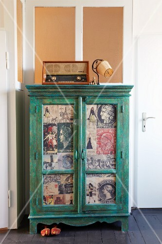 Green cabinet with door panels covered in newspaper clippings in corner of room below transom window