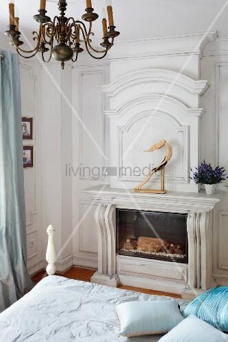 Blick über das Bett auf Kamin mit massgefertigter Holzverkleidung in ...