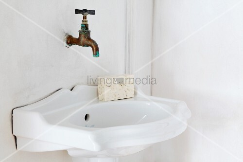 Vintage sink and wall-mounted copper tap in corner of bathroom