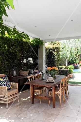 sitzplatz mit bugholzst hlen auf berdachter gefliester terrasse im hintergrund sonniger garten. Black Bedroom Furniture Sets. Home Design Ideas