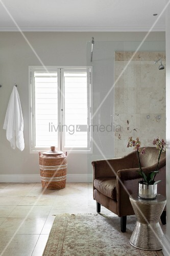Orchid on shiny silver table next to brown armchair in front of elegant, glazed shower area