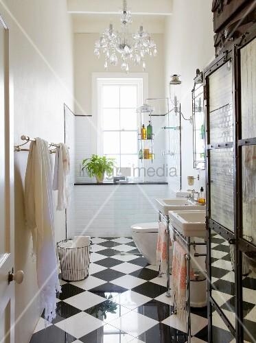 Schmales Bad mit glänzendem Schachbrettmusterboden, Waschbecken im ...