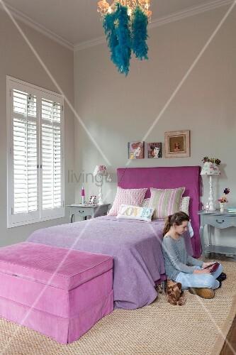 Jugendzimmer In Fliedertönen Und Blauer Federboa An Kronleuchter, Mädchen  Am Boden Sitzend Mit Hund