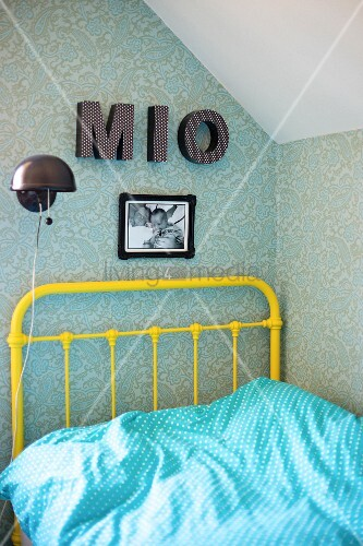 Yellow, vintage metal bed frame, pale blue and white polka-dot bed linen, charcoal wall lamp and decorative letters on patterned wallpaper in corner of teenager's bedroom