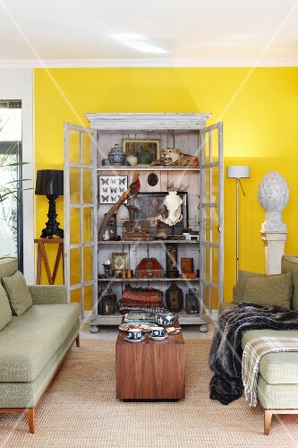 Fifties-style, pale green sofa set and wooden table in front of display cabinet with open doors and view of antique collectors' items in living room with yellow-painted wall