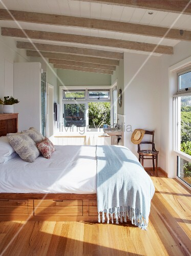 Light-flooded bedroom with drawers below bed in holiday home with parquet floor and pale, varnished wood-beamed ceiling