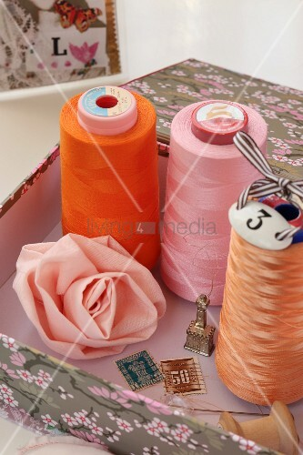 Reels of thread and hand-sewn fabric rose