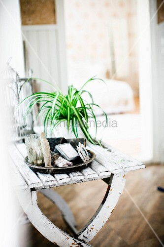 Tray of various ornaments and potted ornamental grass on white-painted table