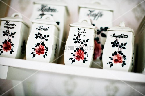 China spice boxes with rose motif on shelf
