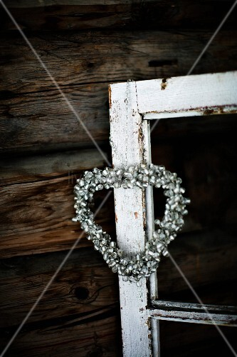 Ornamental, heart-shaped wreath hanging on disused window frame