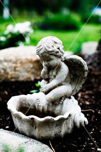 Stone bird bath with cherub figurine outside