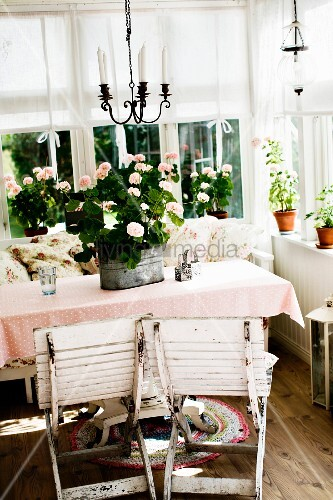 Weathered, wooden folding chairs painted white in front of potted plants on tablecloth on table in corner of loggia