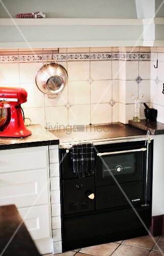 Black, vintage kitchen cooker against white splashback with accent tiles in simple kitchen