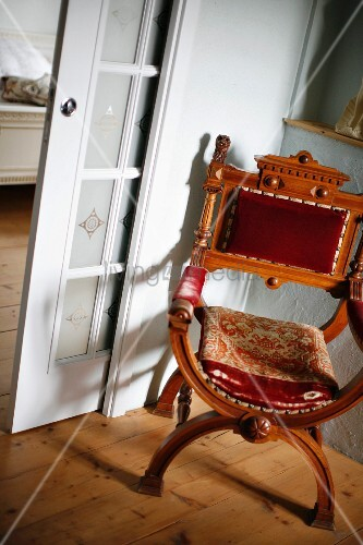 Regency-style, antique chair in corner next to lattice, sliding door