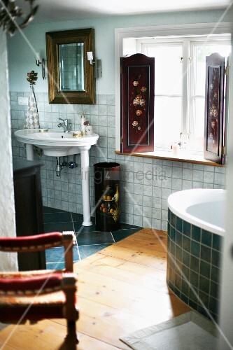 Vintage, pedestal sink on column-style legs next to window with painted interior shutters in bathroom with wooden and tiled floor