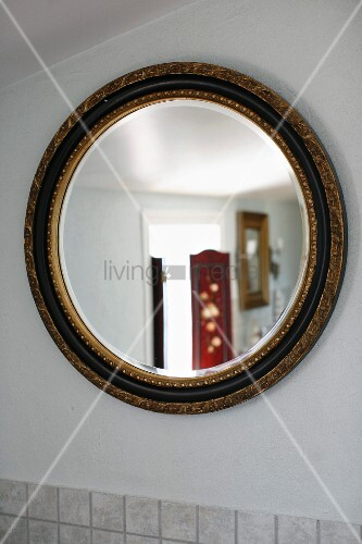Round mirror with gilt frame on white wall