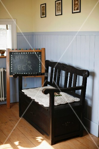 Rustic, dark wood bench next to blackboard in corner with pale grey wainscoting