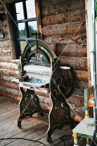 Vintage sewing machine against outside wall of log cabin