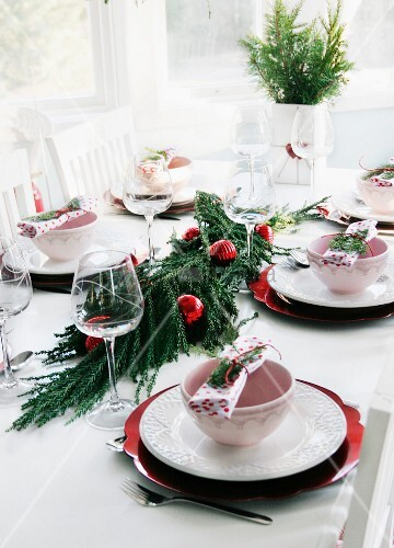 Table set for restive lunch with conifer branches and red Christmas baubles arranged in centre