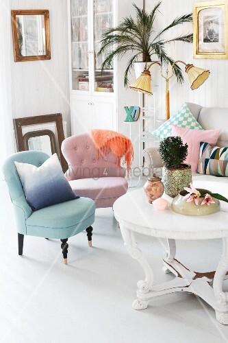 Sessel in Pastellfarben und weisser, runder Couchtisch mit ...