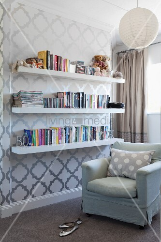 Reading corner with pale armchair next white bookshelves mounted on wallpaper with geometric pattern
