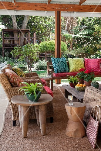 Furnished terrace with wicker armchair and bench with scatter cushions in various colours