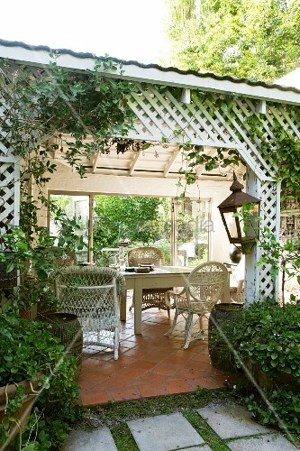 Weisse korbst hle und holztisch auf berdachter terrasse mit umlaufendem kreuzf rmigem - Holztisch terrasse ...