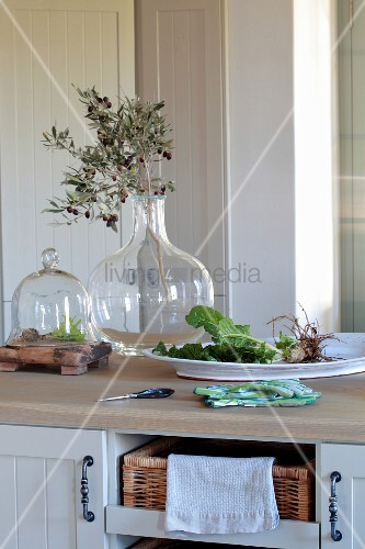 Olive Branch In Glass Vase Next To Bowl Of Fresh Vegetables On