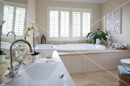 Elegant bathroom with twin washstand and large oval bathtub